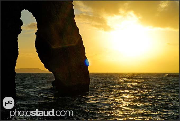Sun setting at Durdle Door natural limestone arch, Jurassic Coast World Heritage site, Dorset, England, Europe