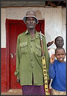 Children surrounding a policeman with gun in Baragoi, Northern Kenya