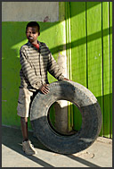 African boy playing with old tire, Maralal, Northern Kenya