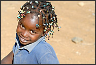 Smiling Kenyan girl with colorful hairstyle, Suguta Marmar, Kenya