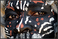 Close up portrait of dark-painted Kikuyu warrior, Kenya
