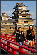 Two Japanese girls walking on wooden Uzumi-Bashi bridge with Matsumoto castle in background, Matsumoto, Japan