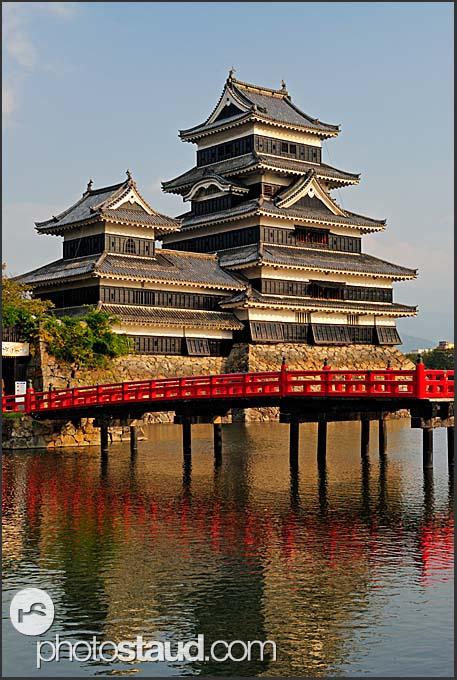 Matsumoto castle and red Uzumi-Bashi bridge reflecting in pond, Matsumoto, Japan