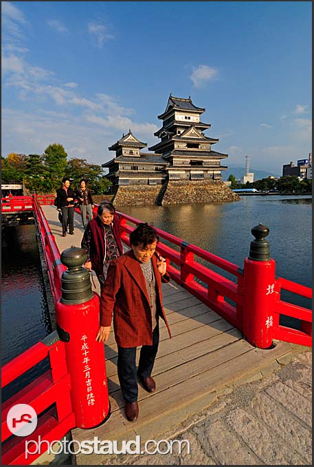 Elderly Japanese tourists walking on wooden Uzumi-Bashi bridge  with Matsumoto castle in background, Matsumoto, Japan