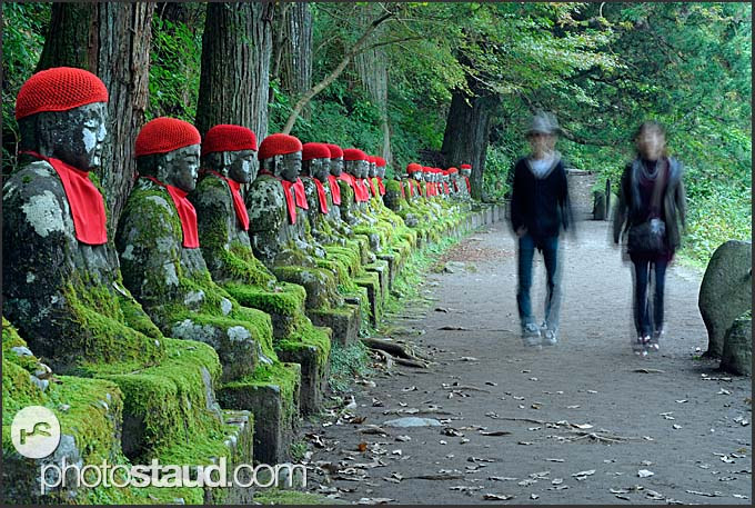 Japanese tourists walking along a line of Jizo statues, Narabi-jizo, Bake-jizo, Nikko National Park, Japan