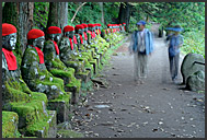 Japanese tourist walking along row of Jizo statues, Narabi-jizo, Bake-jizo, Nikko National Park, Japan