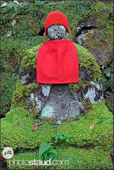 One of Narabi-jizo statues with red hat and bib covered in moss, Nikko National Park, Japan