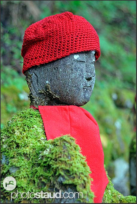 Narabi-jizo statues with red hat and bib covered in moss, Nikko National Park, Japan
