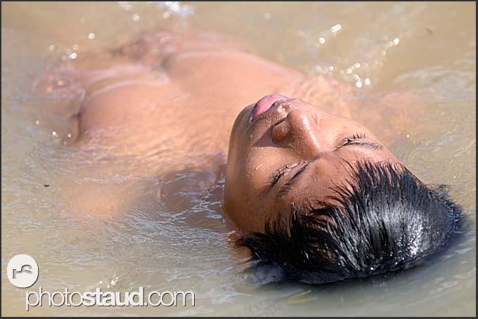 Cambodian boy swimming in Siem Reap river, Cambodia