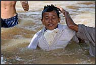 Cambodian boy wearing polystyrene instead of life vest in Siem Reap River, Cambodia