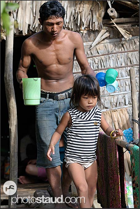 Father and daughter in front of cottage, Cambodia