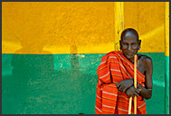 Old Samburu man in red cover resting before colorful butchery wall, South Horr, Kenya