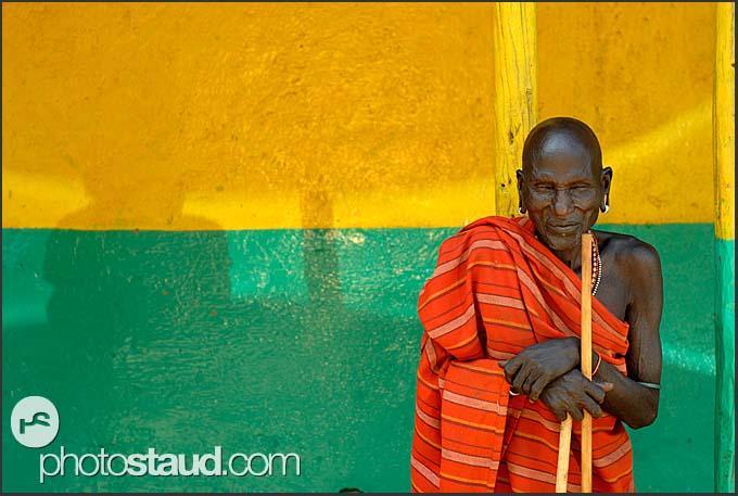 Old man and shadow - Samburu man in red blanket resting before colorful butchery wall, South Horr, Kenya