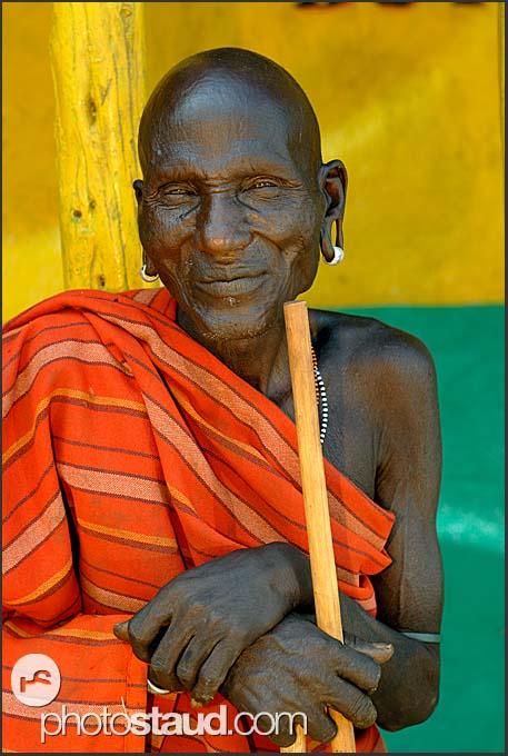 Old Samburu man in red cover resting before colorful butchery wall, South Horr, Kenya