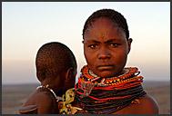 Samburu woman wearing tribal bead ornaments sitting inside her cottage, Kenya