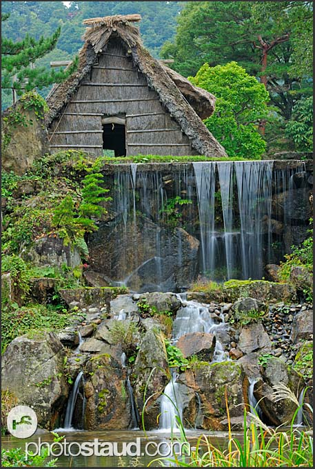 Waterfall and gassho zukuri farm house, Shirakawa village, UNESCO World Heritage site, Japan