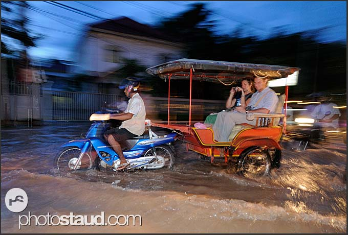 Tourists riding through flooded streets of Siem Reap, Cambodia
