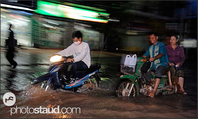 Cambodian people riding motorcycles in flooded streets of Siem Reap, Cambodia