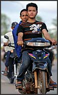 Cambodian man riding motorbike from local market, Siem Reap, Cambodia