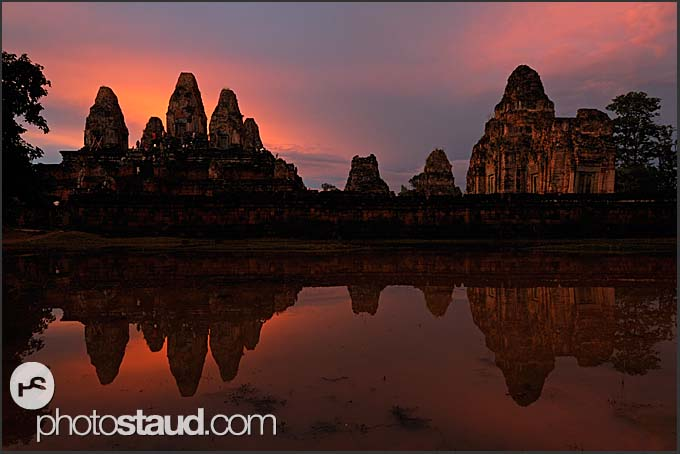 Ta Keo Temple of Angkor reflected in water at sunset, Cambodia
