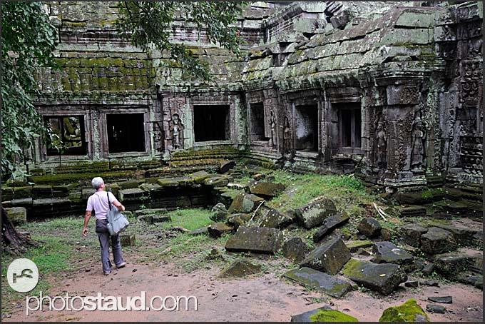 Tourist exploring Ta Prohm Temple, Angkor, Cambodia
