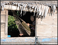 Resting in hammock by the window, floating village on Tonle Sap Lake, Cambodia