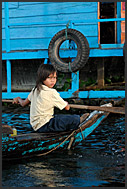 Little girl removing water from her boat, Tonle Sap Lake, Cambodia