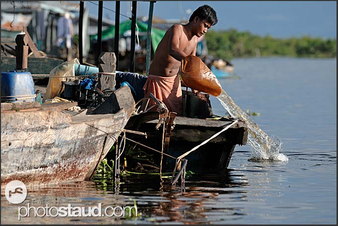 Man removing water from her boat, Tonle Sap Lake, Cambodia