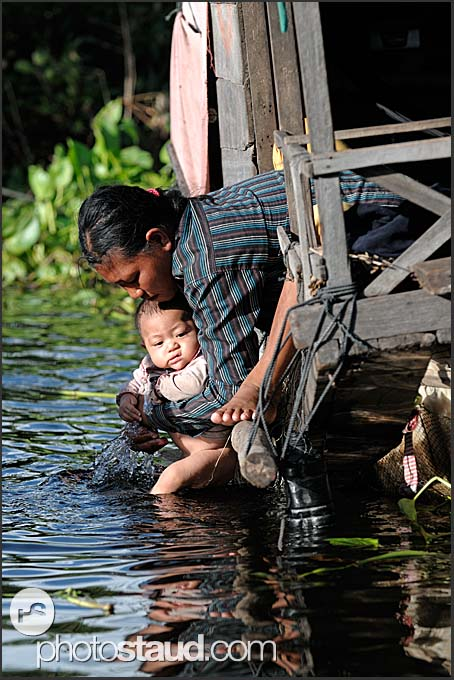 Mother washing her son in the waters of Tonle Sap Lake, Cambodia