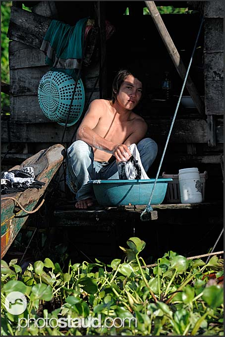 Young man washing up, floating village of Tonle Sap Lake, Cambodia