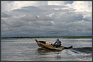 Man on a boat, floating village, Tonle Sap Lake, Cambodia