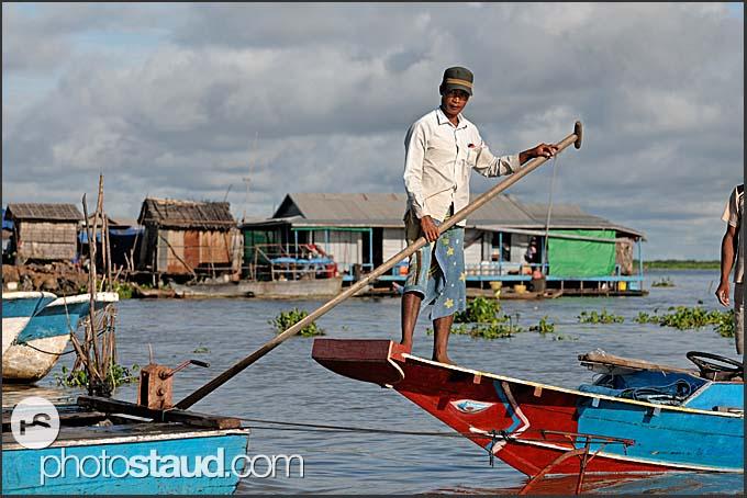 Man on a boat, floating village, Tonle Sap Lake, Cambodia