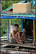 Young man squatting on a boat, Tonle Sap Lake, Cambodia