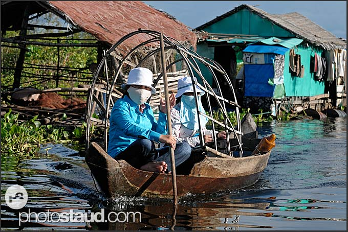 Two women on a boat, floating village, Tonle Sap Lake, Cambodia
