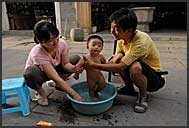 Chinese couple washing their son on the street of Tunxi, Huangshan city, Anhui, China