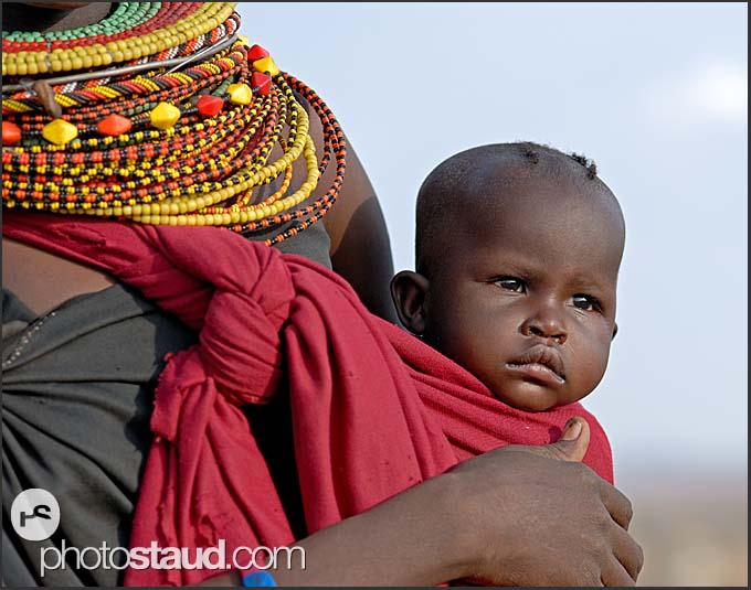 Turkana tribeswoman carrying her child, Northern Kenya
