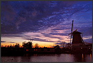 Traditional Dutch windmill and heavy clouds reflecting in Vecht river at night, Vreeland, The Netherlands, Europe