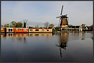Traditional Dutch windmill and modern houseboats at Vecht river, Vreeland, The Netherlands, Europe