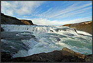 Tourists looking up at Gullfoss waterfall, Iceland