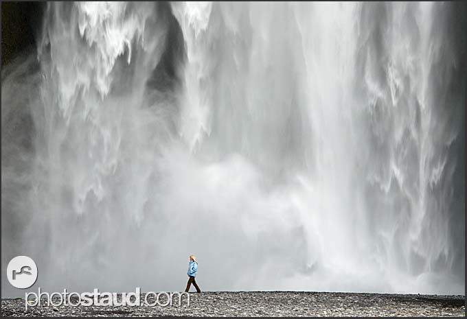 Tourist walking under Skogafoss waterfall, Iceland