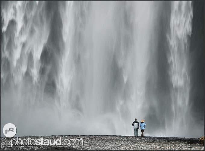 Couple under Skogafoss waterfall, Iceland