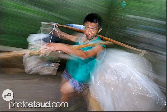 Porter carrying garbage off the Yellow Mountains, Huangshan, Anhui, China