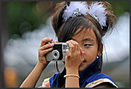 Little Japanese girl in traditional costume taking photographs at Michinoku YOSAKOI Festival, Sendai, Japan