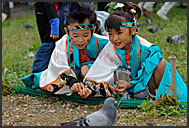 Little Japanese girl in traditional costume feeding pigeons during Michinoku YOSAKOI Festival, Sendai, Japan