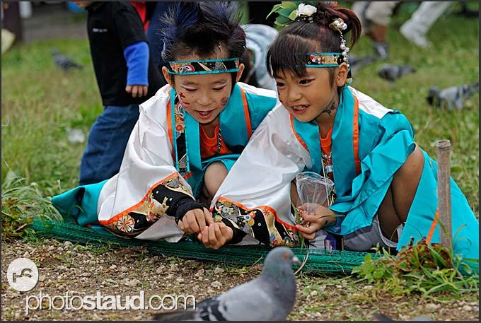 Japanese children in traditional costume feeding pigeons during Michinoku YOSAKOI Festival, Sendai, Japan