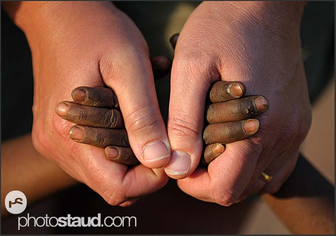 Hands in hands - tourist holding hands of African children, Zambia