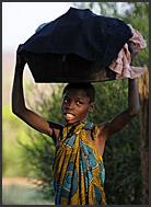 Zambian child carrying laundry on head, Zambia
