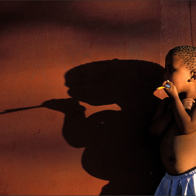 Little girl and shadow in Den/ui village, Bushmanland, Namibia