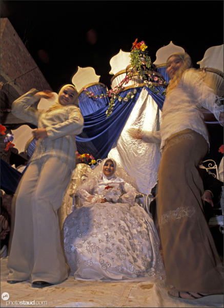 Two girls dance around bride at Islamic wedding, El Qasr, Dakhla Oasis, Western Desert, Egypt