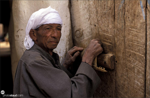 Bedouin opens the door of his house using a special wooden key, Balat village, Dakhla Oasis, Libyan Desert, Egypt
